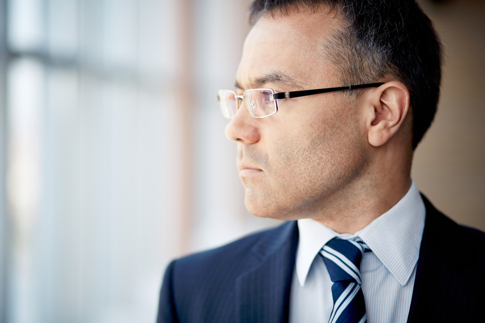 Portrait Of Thoughtful Businessman Looking Through Window