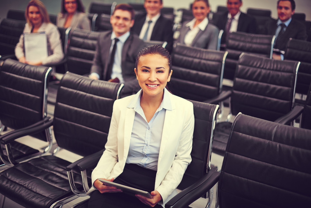 Image Of Businesswoman Looking At Camera On Background Of Co-workers Sitting In Rows At Seminar