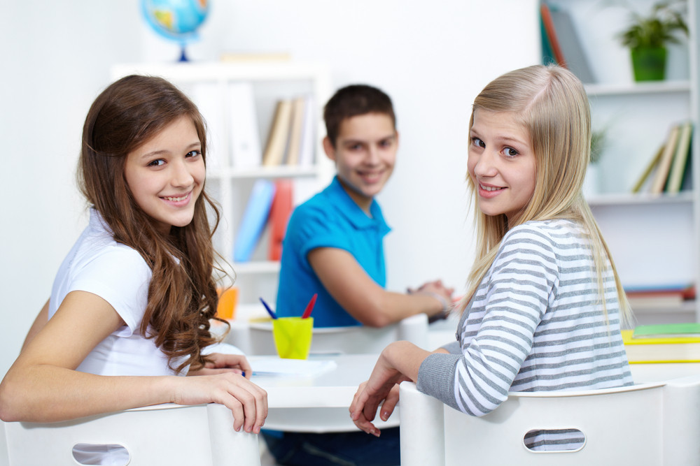 Teenage Girls Looking At Camera With Happy Lad On Background