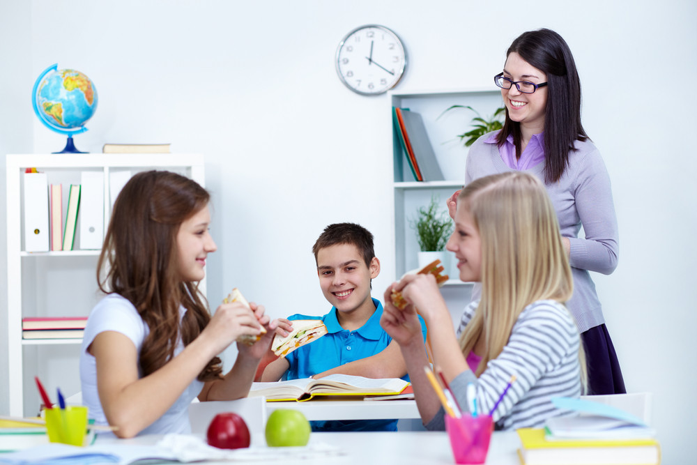 Hungry Students Eating Sandwiches During Break In College With Their Teacher Near By
