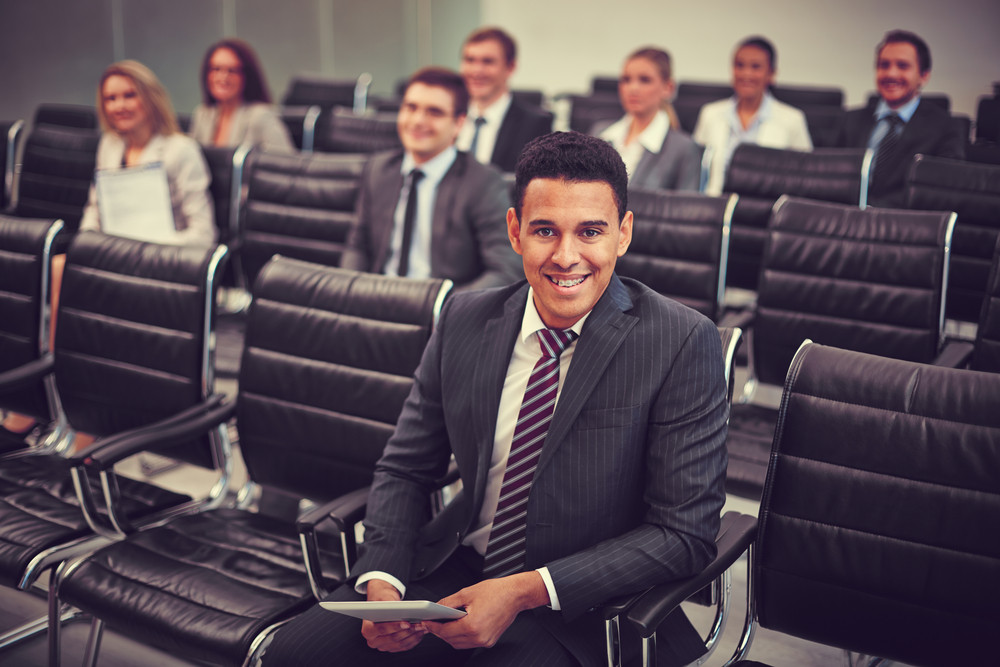 Image Of Business Partners Sitting In Rows At Seminar With Smiling Man On Foreground