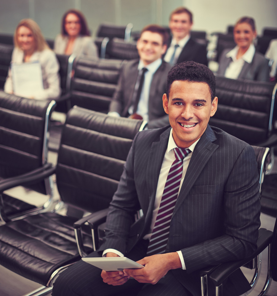 Image Of Smiling Businessman Sitting In Row With His Colleagues On Background