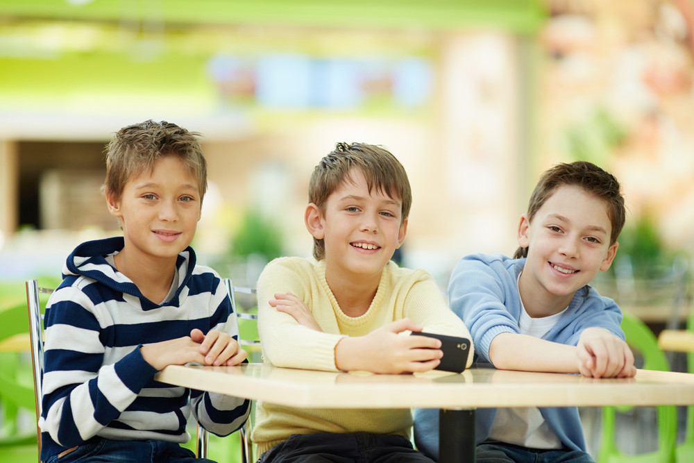 Portrait Of Three Schoolboys Sitting At Table