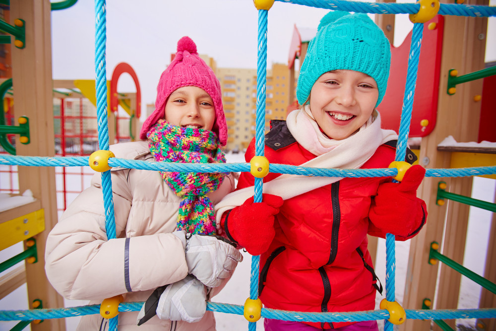 Happy Girls In Winterwear Looking At Camera While Having Fun On Playground