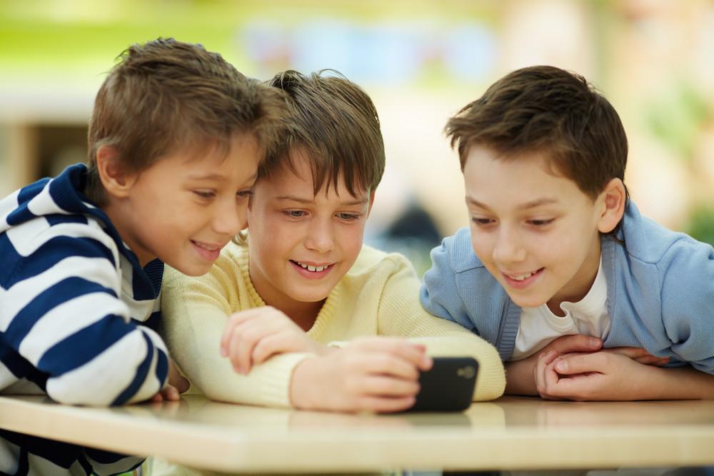 Three Boys Surfing The Net On Smartphone