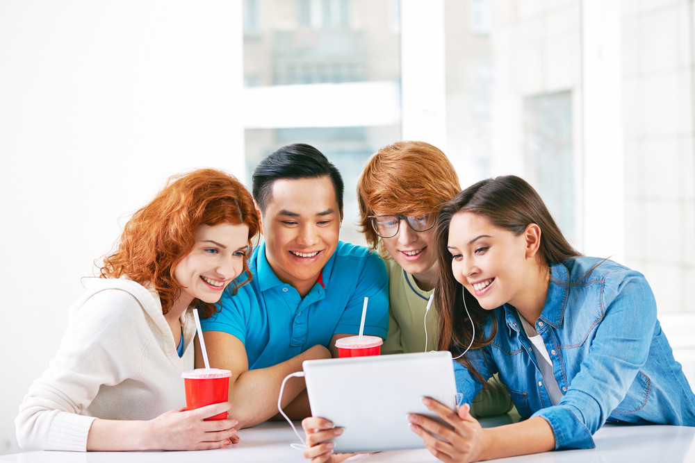 Company Of Smart Groupmates Using Touchpad While Having Drink