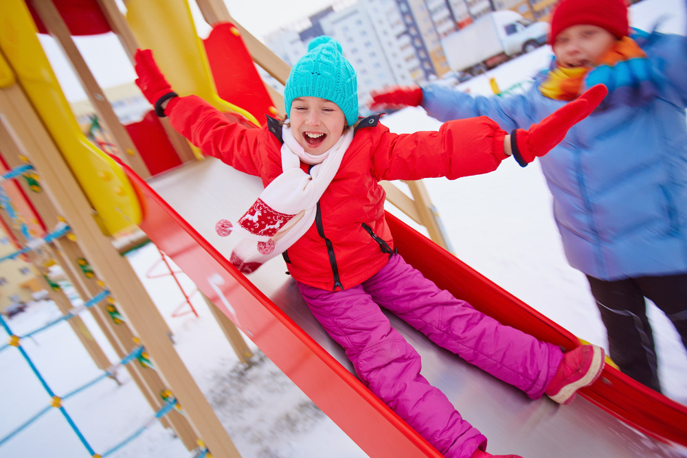 Happy Girl In Winterwear Playing Outside With Her Friend Near By