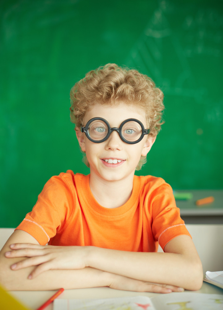 Portrait Of Happy Schoolboy In Eyeglasses Looking At Camera