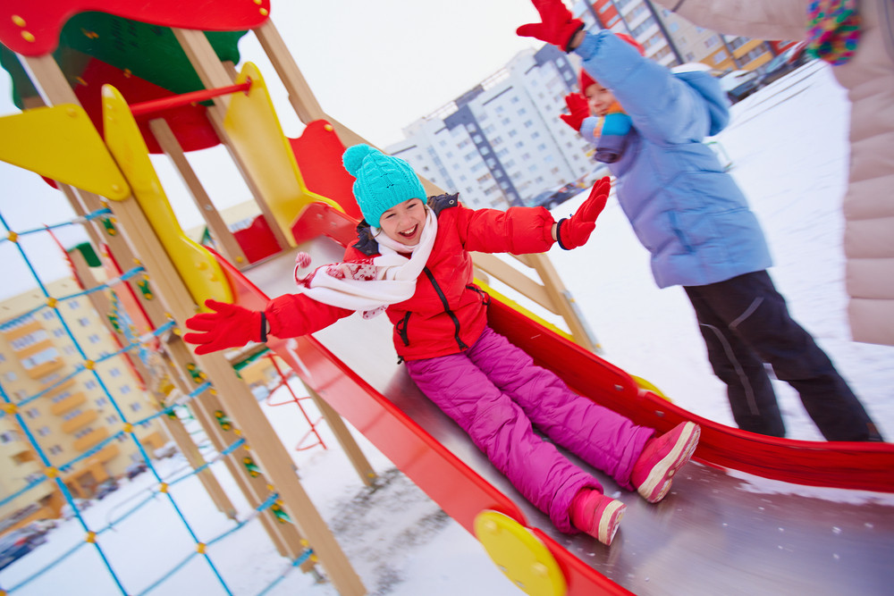 Happy Girl In Winterwear Playing Outside With Her Friends Near By