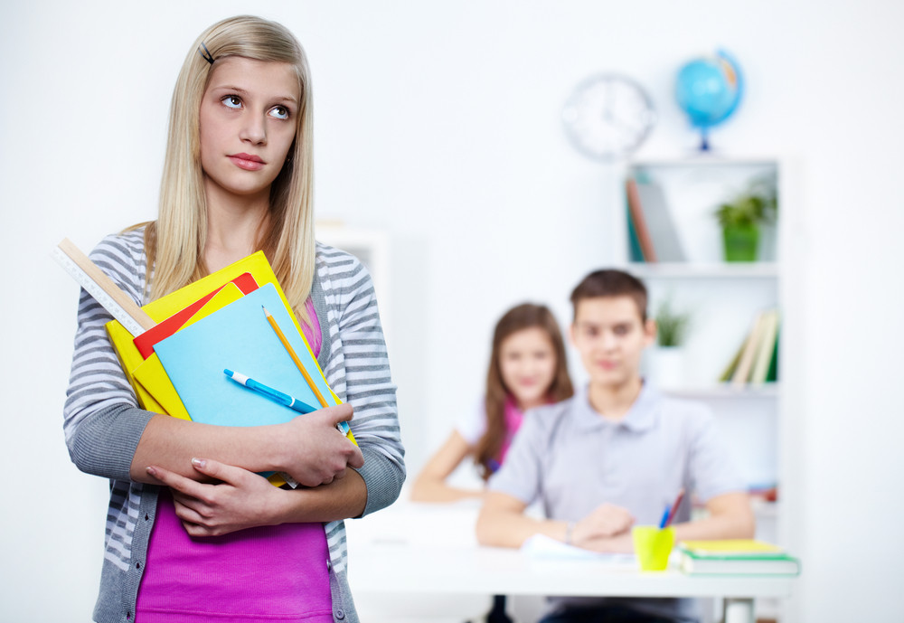 Portrait Of Pensive Teenage Blonde With School Objects