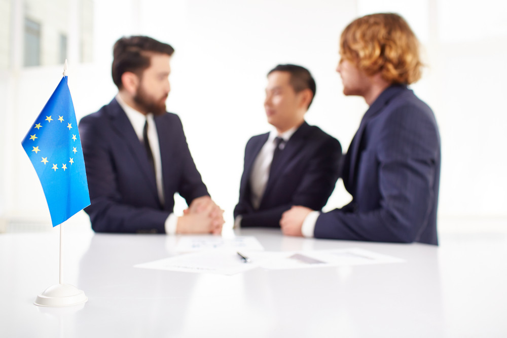 Image Of European Flag On Workplace With Three Partners Negotiating On Background