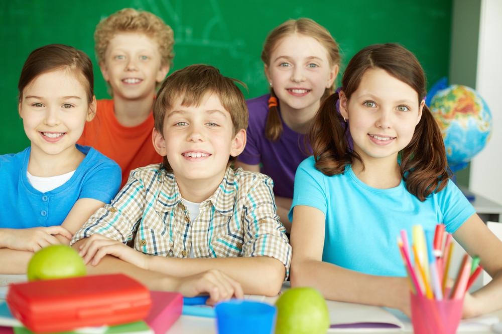 Portrait Of Cute Schoolchildren Looking At Camera In Classroom