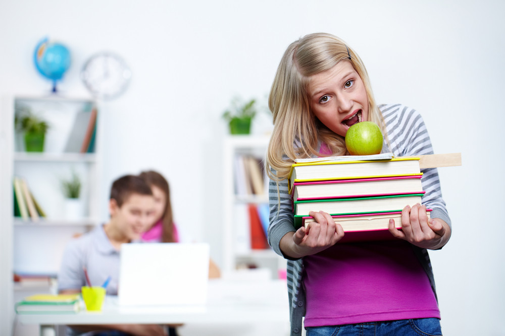Portrait Of Cute Teenage Blonde With School Objects Looking At Camera