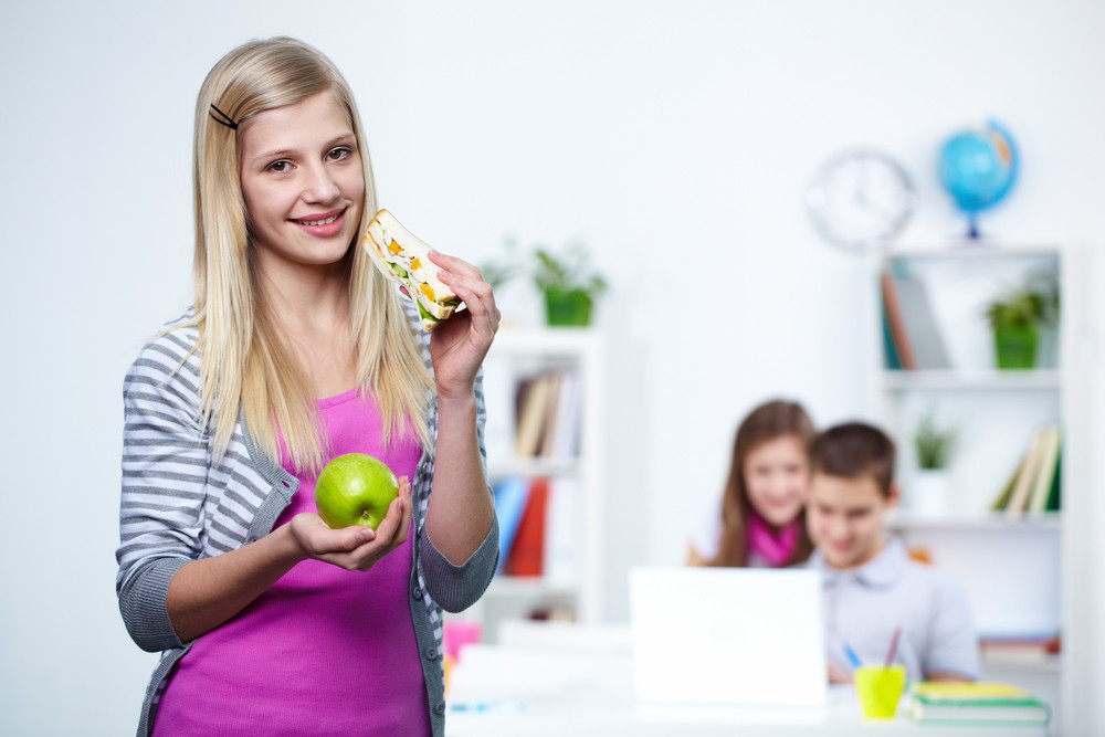 Portrait Of Cute Teenager With Apple And Sandwich Looking At Camera