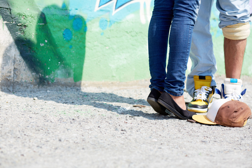 Image Of Young Couple Legs On Background Of Graffiti Wall