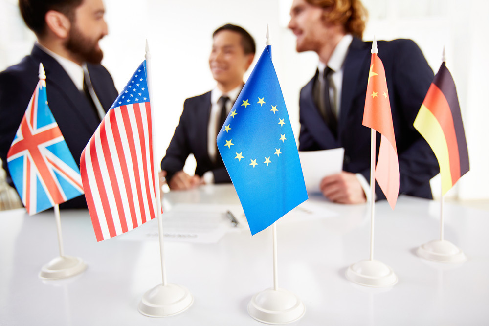 Image Of Several Flags Of Different Countries On Workplace With Three Partners Negotiating On Background