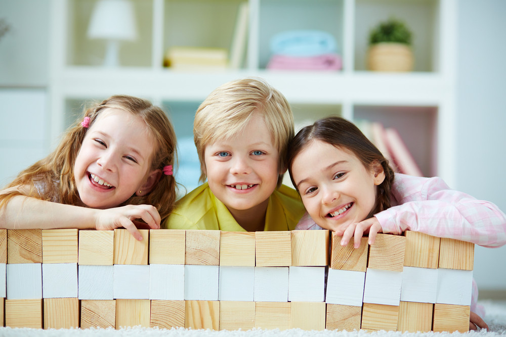 Three Little Friends With Wooden Bricks Looking At Camera