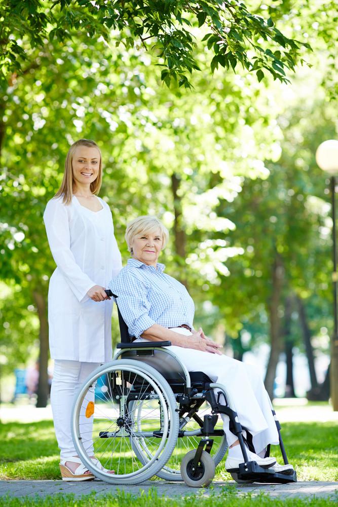 Pretty Nurse And Senior Patient Walking In Park