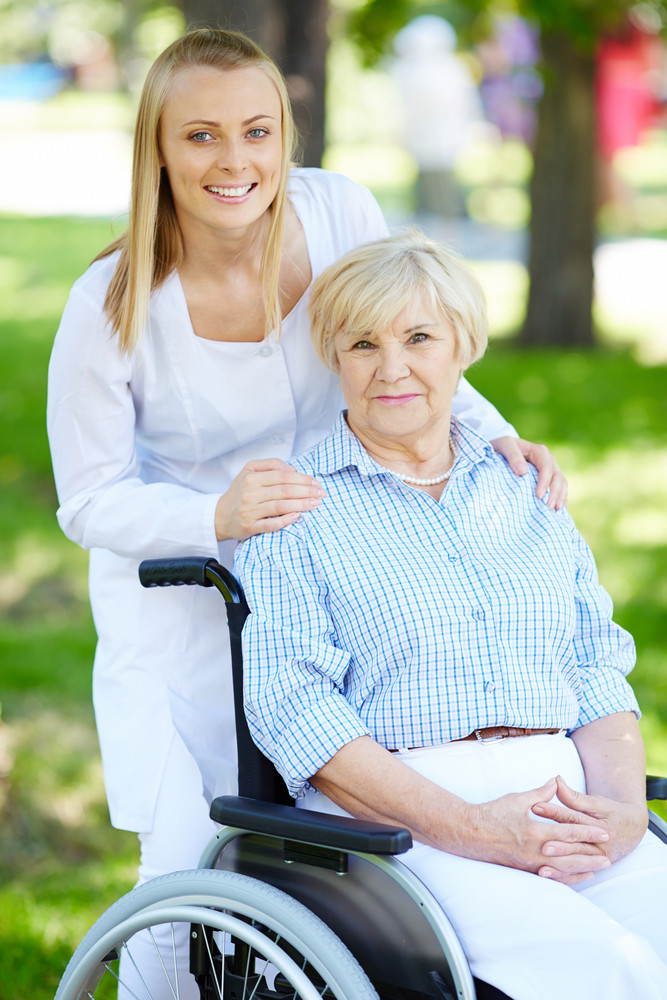 Pretty Nurse And Senior Patient In A Wheelchair Looking At Camera In Natural Environment