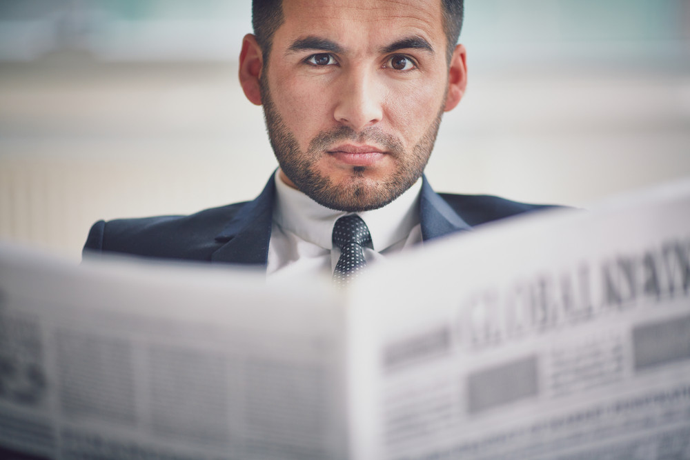 A Young Serious Businessman With Newspaper Looking At Camera