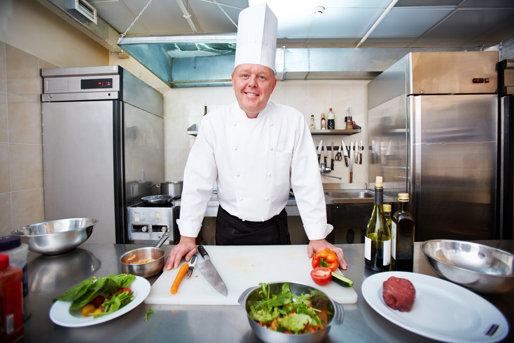 Image Of Male Chef Looking At Camera In The Kitchen