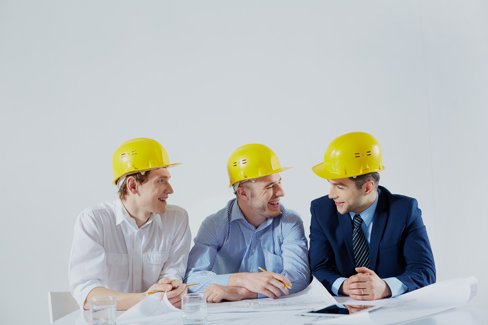 Copy-spaced Image Of Cheerful Engineers Sharing The Ideas Over White