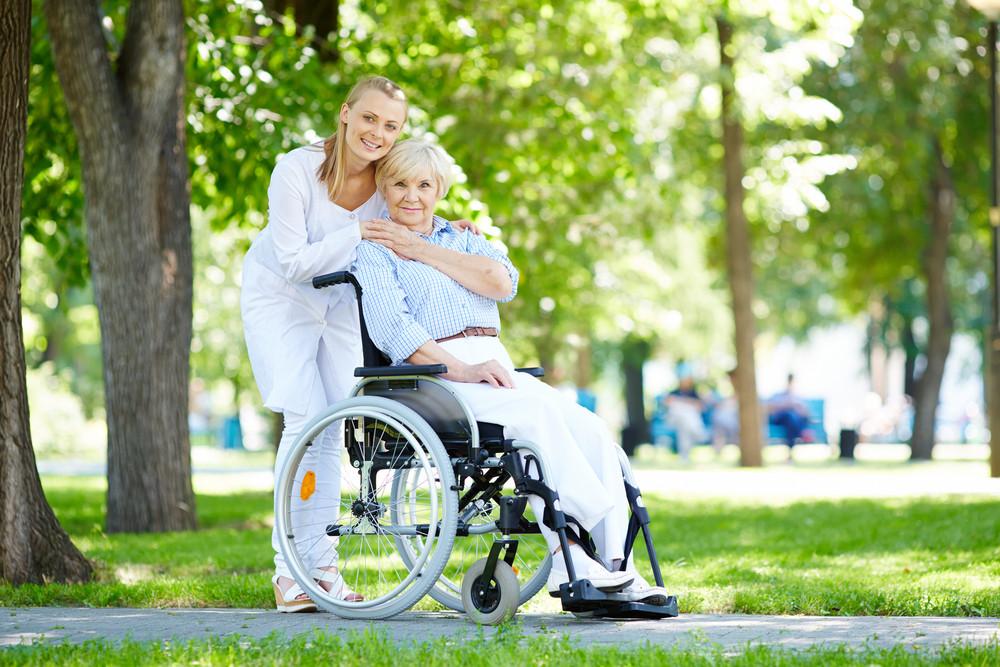 Pretty Nurse Taking Care Of Senior Patient In A Wheelchair