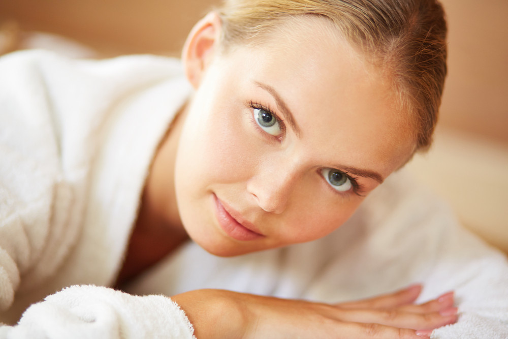 Portrait Of Young Female In White Bathrobe Looking At Camera
