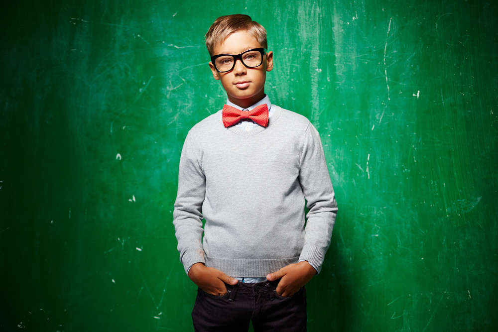 Serious Schoolboy In Eyeglasses And Grey Pullover With Red Bowtie Standing By The Blackboard And Looking At Camera