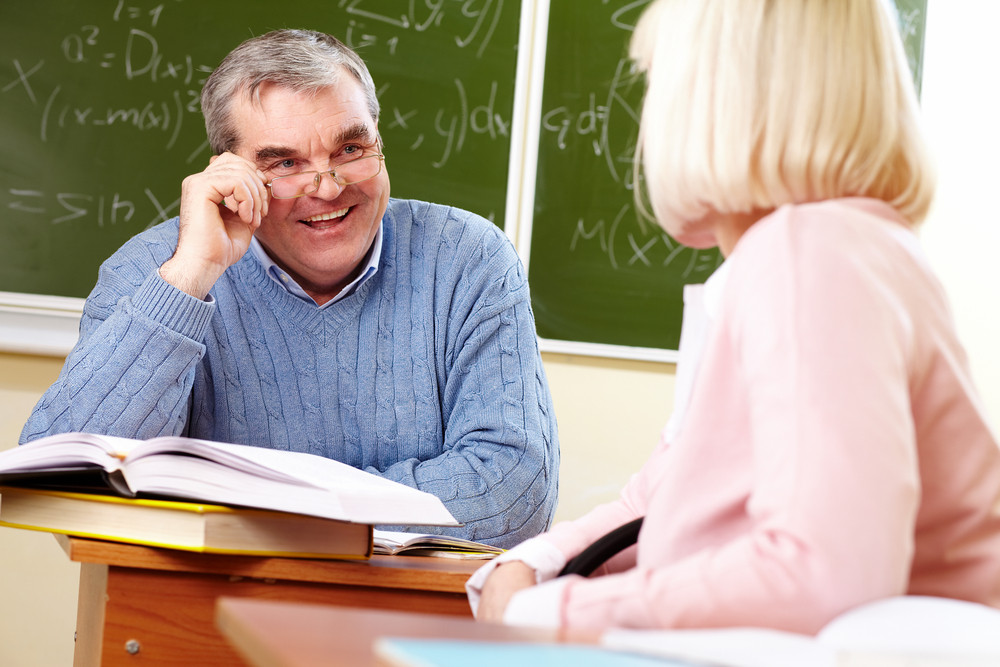 Portrait Of Mature Man Speaking To Aged Female During Training Course