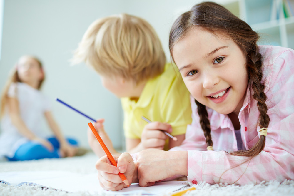 Pretty Little Girl Looking At Camera While Lying On The Floor And Drawing With Her Friends Behind