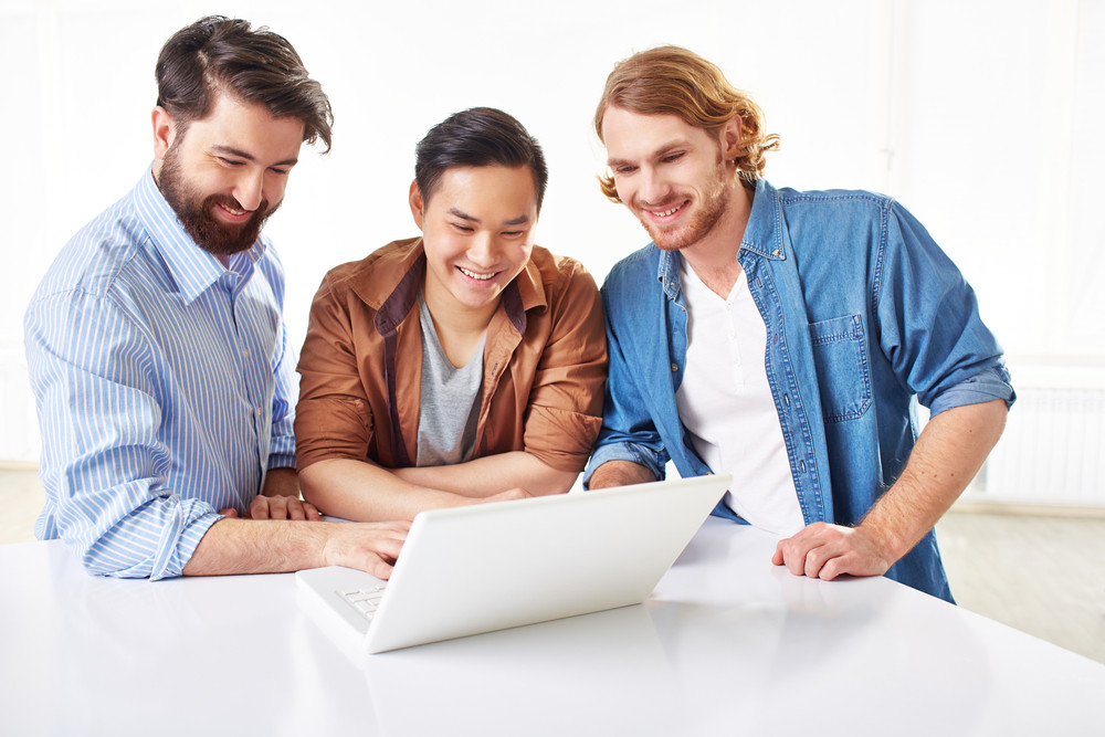 Smiling Men In Casual Using Laptop