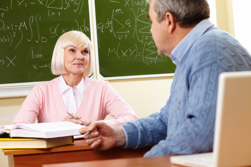 Portrait Of Mature Man Speaking To His Teacher During Training Course