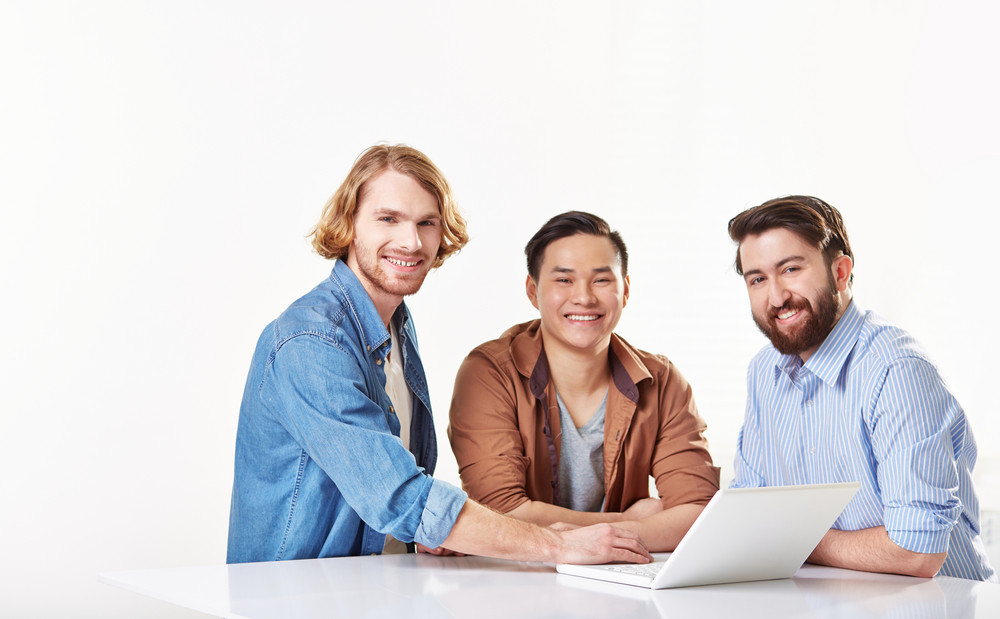 Group Of Friendly Men With Laptop Looking At Camera