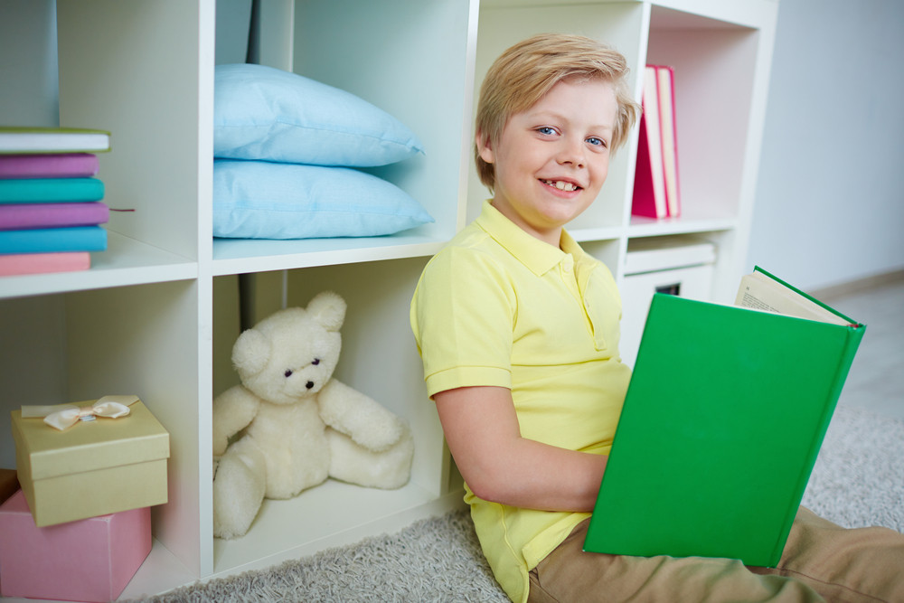 Portrait Of Clever Boy Reading Book At Home