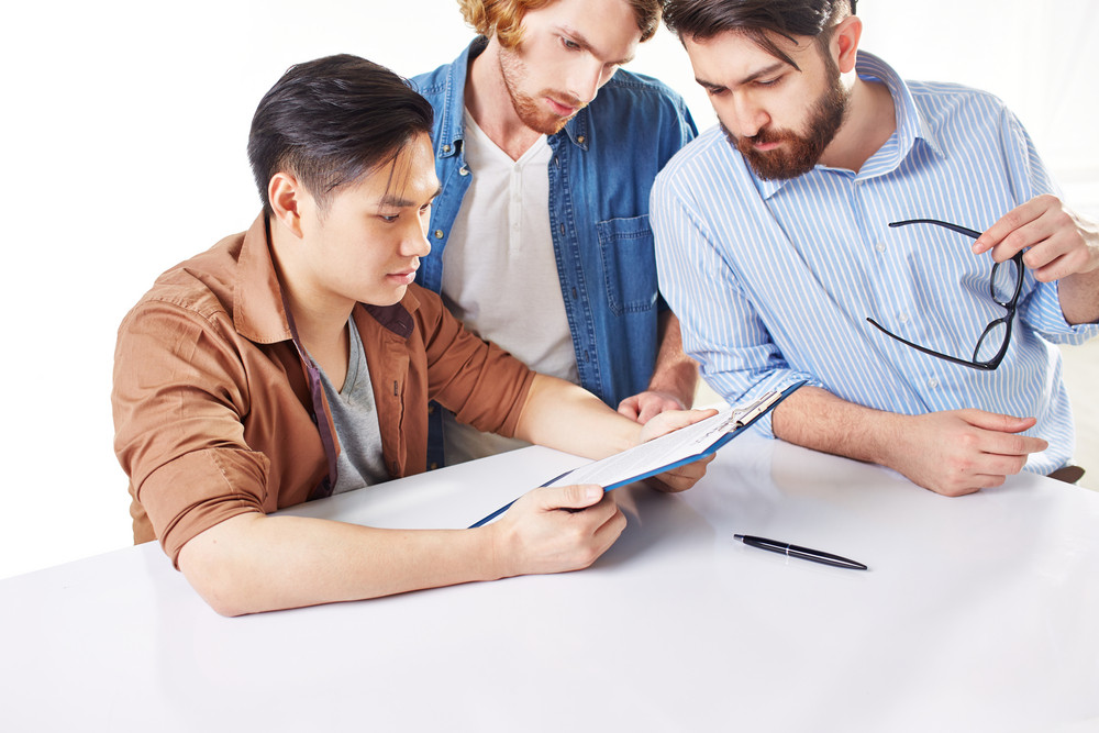 Group Of Businessmen In Casual Reading Contract