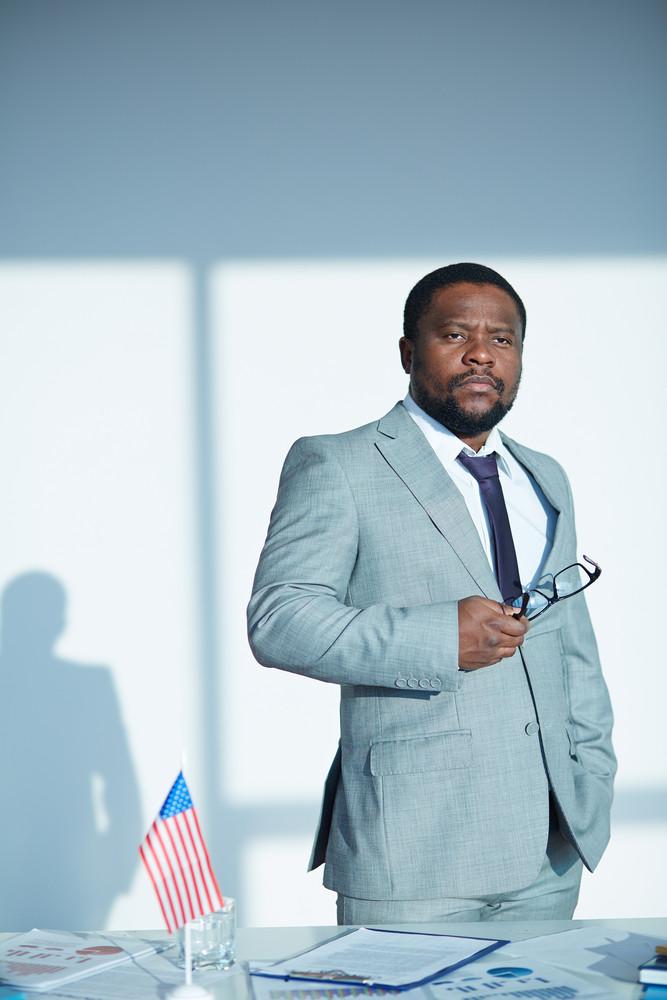 African-american Employee In Suit Standing In Office