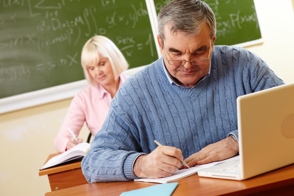 Senior Man In Eyeglasses Carrying Out Written Task In Classroom