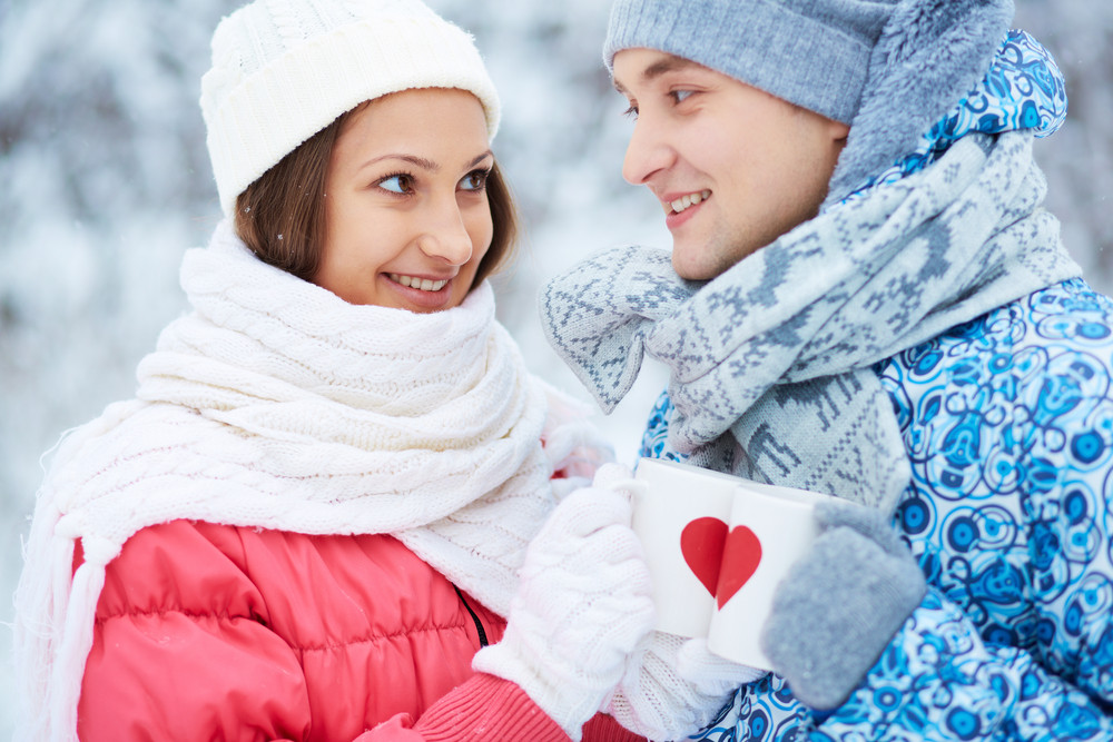 Young Couple Holding Cups With Red Hearts And Toasting In Winter