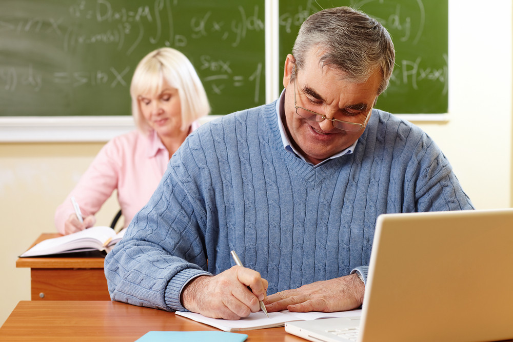 Senior Man With A Cheerful Smile Doing The Task In Classroom