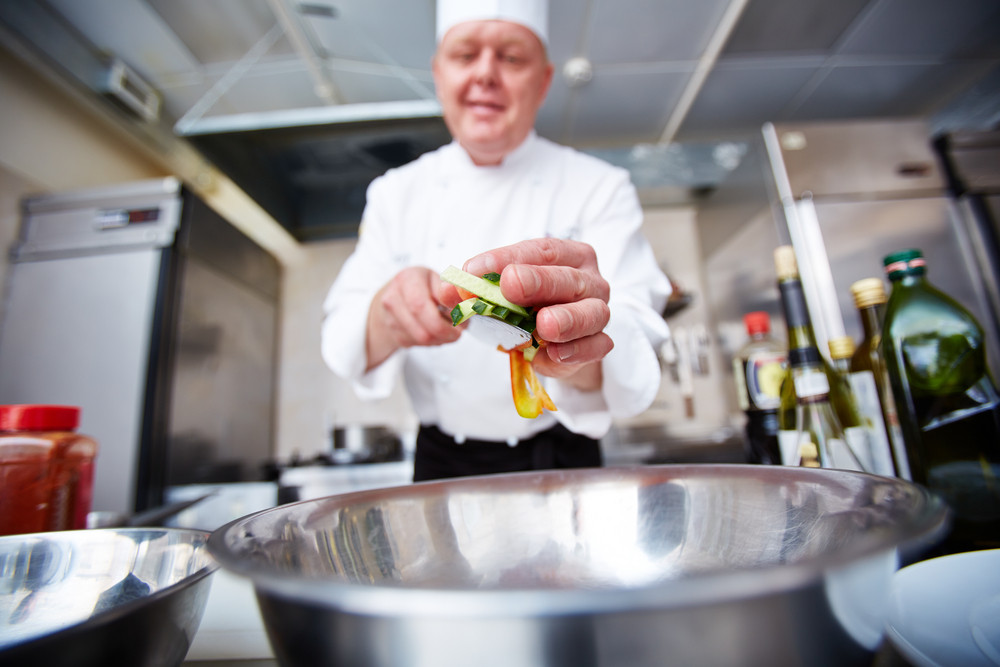 Image Of Male Chef Putting Cut Vegetables In Bowl In The Kitchen