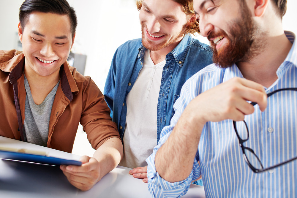 Group Of Happy Businessmen In Casual Reading Contract