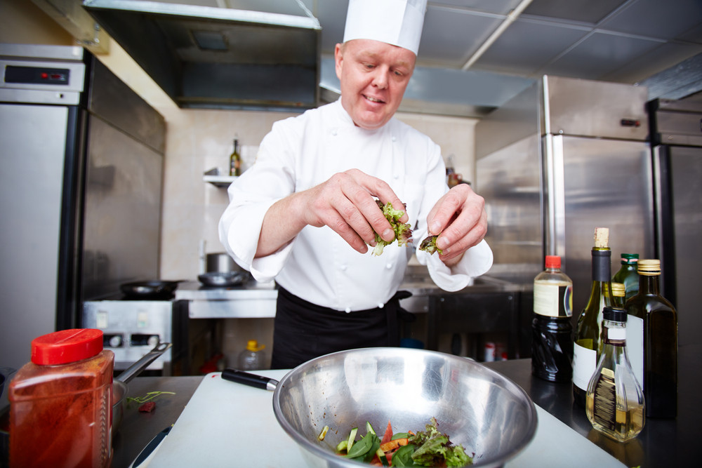 Image Of Male Chef Cooking Salad In The Kitchen