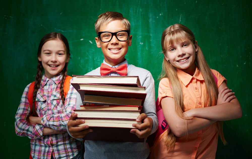 Happy Schoolboy With Stack Of Books And Two Girls Standing By The Blackboard And Looking At Camera