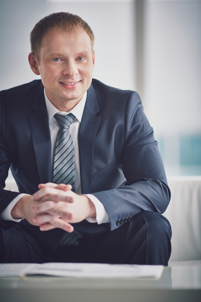 Smiling Businessman In Suit Looking At Camera