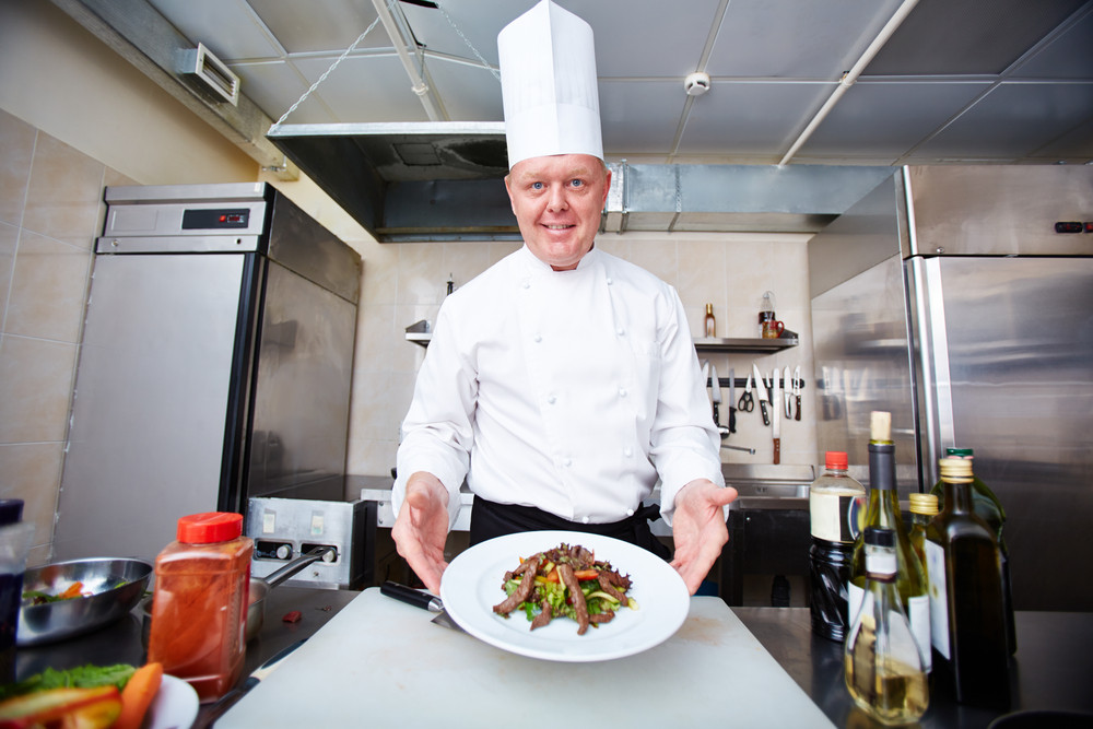 Image Of Male Chef Serving Salad On Plate