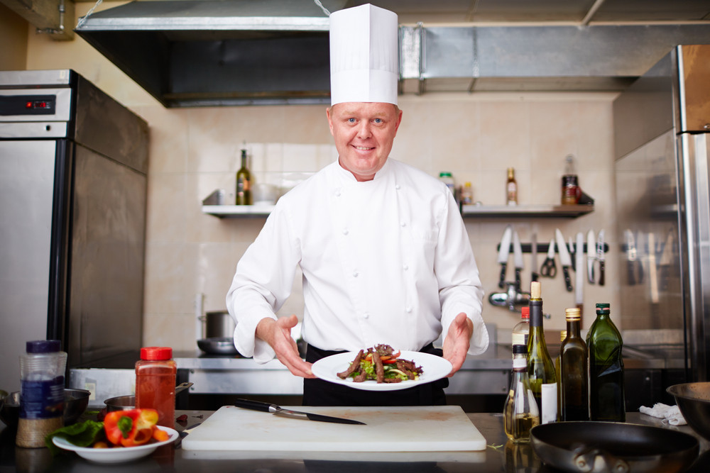 Image Of Male Chef Holding Plate With Salad And Looking At Camera