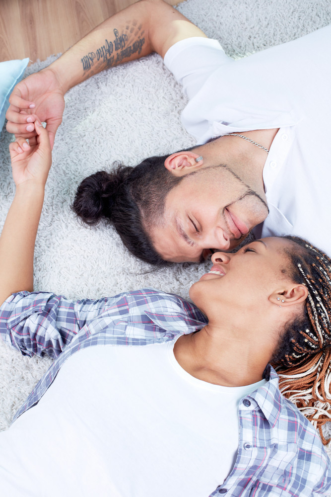Image Of Young Guy And His Girlfriend Lying On The Floor And Holding By Hands