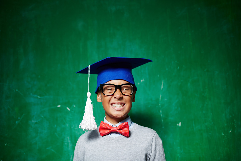 Smiling Kid In Eyeglasses And Graduation Hat Looking At Camera By The Blackboard