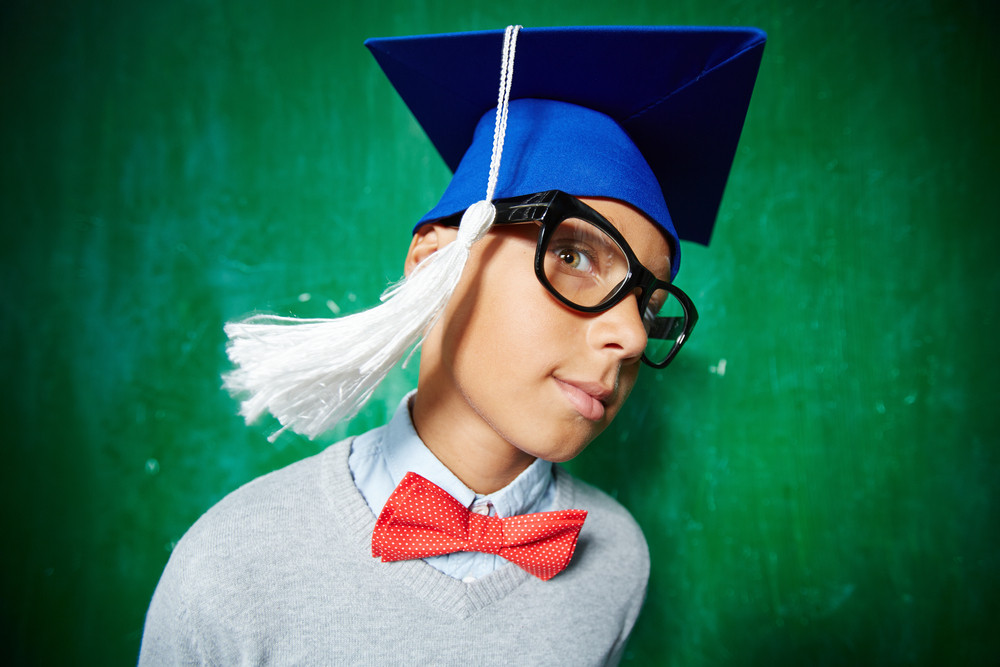 Cute Schoolboy In Eyeglasses And Graduation Hat Looking At Camera